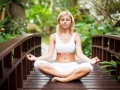 Beautiful woman meditating in the tropical garden.